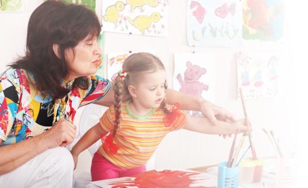 teacher teaching the little girl to paint